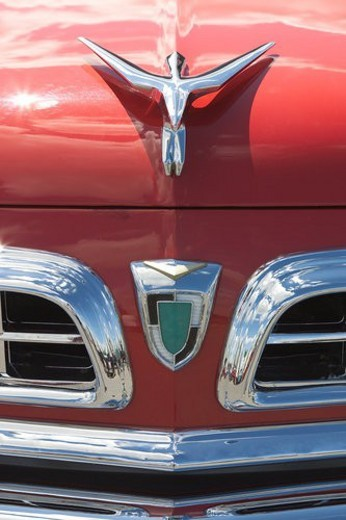 front view of old red  Chrysler, detail of front hood and grille, with silver chrome trim, logo removed : Stock Photo