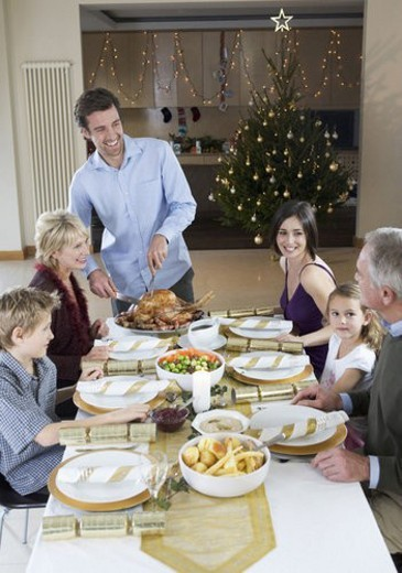 A family sitting down for Christmas dinner : Stock Photo