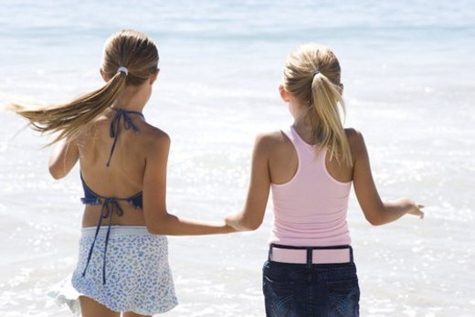 Two young girls running on the beach hand in hand : Stock Photo
