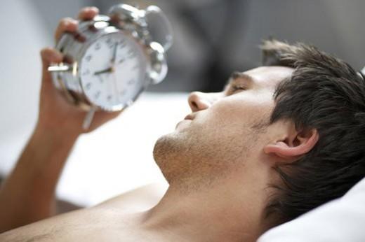 Young man looking at his alarm clock : Stock Photo