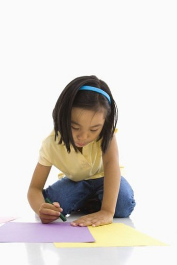 Asian girl sitting on floor coloring on paper. : Stock Photo