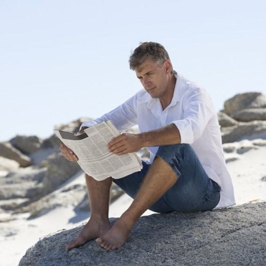 Stock Photo: 4029R-338625 A man sitting on rocks reading a newspaper