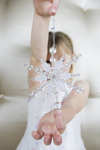 Young girl in a party dress, holding a Christmas decoration : Stock Photo