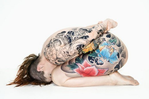 Nude caucasian woman with tattoos sitting on floor. : Stock Photo