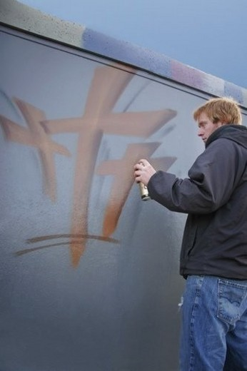 Stock Photo: 4029R-342737 Man spray paints on wall