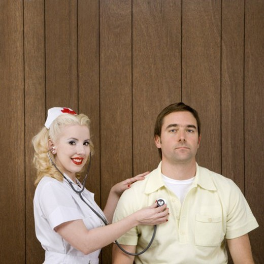 Caucasian mid-adult female nurse  checking male s heartbeat by wood paneling. : Stock Photo