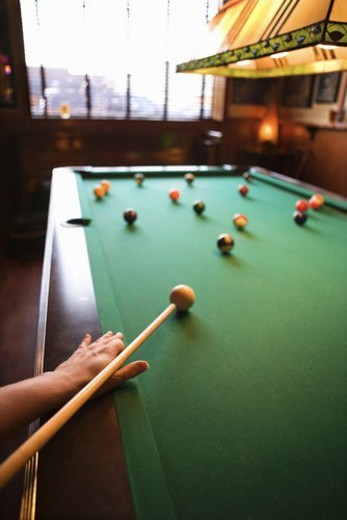 Woman s hand preparing to hit pool ball while playing billiards. : Stock Photo