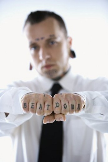 Stock Photo: 4029R-343210 Caucasian mid-adult man with tattoos and piercings holding out fists reading beat down.