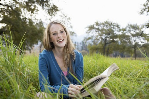 Teenage girl reading book in field : Stock Photo