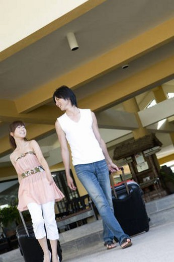 Young couple carrying suitcases, smiling, Saipan, USA : Stock Photo