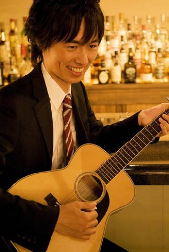 Stock Photo: 4029R-346619 Businessman playing guitar at the bar