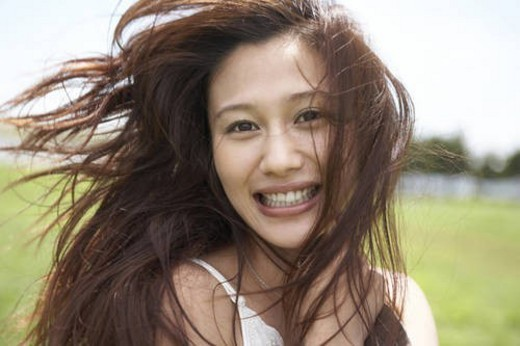 Young Woman in Field, Her Hair Blowing in Wind, Looking at Camera : Stock Photo