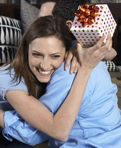 Mid-Adult Woman with Present Hugging Boyfriend : Stock Photo