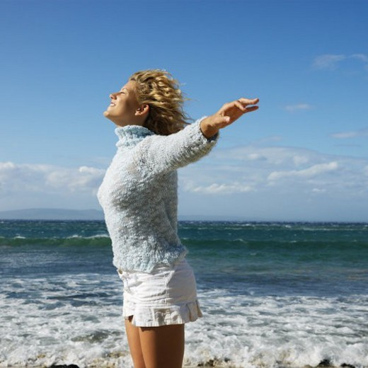 Pretty young blond woman standing on Maui, Hawaii beach with arms out to side and wind blowing hair smiling. : Stock Photo