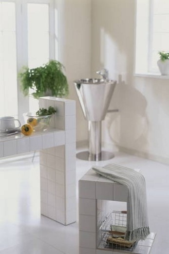 A modern kitchen with tiled walls and a hand basin : Stock Photo