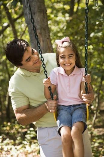 Hispanic father pushing daughter on swing. : Stock Photo