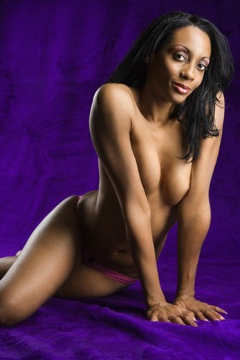 Topless mid-adult African American woman in hot pink underwear posing on purple background looking at viewer. : Stock Photo