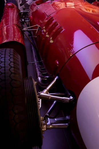 Stock Photo: 4029R-350564 Detail of red Ferrari, race  car, front  side view, showing wheel and  struts