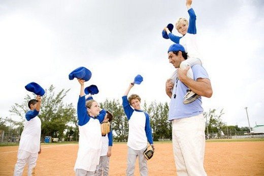 Young boy being carried on the shoulders of baseball coach : Stock Photo
