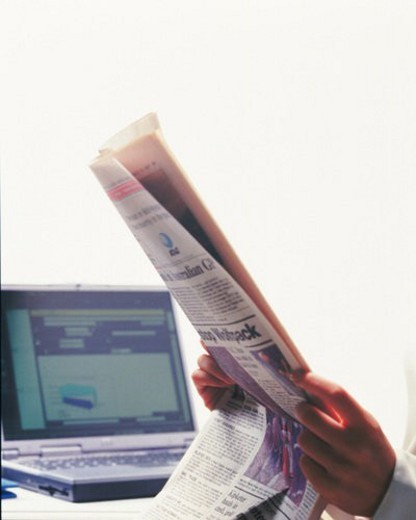 Hands holding news paper at the desk, Portrait, Side View : Stock Photo