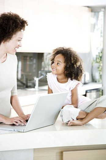 Mother using laptop in kitchen while young daughter looks on smiling : Stock Photo