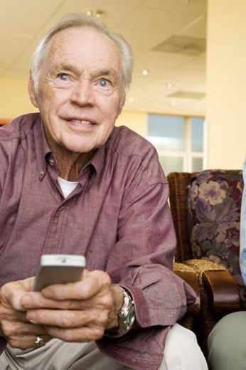 An elderly man using a TV remote control : Stock Photo