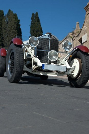 Low front view of white antique Mercedes with red trim on wheel arches, showing head lamps, grille and wheels, on road in Assisi, at Mille Miglia, with blue sky and cypress trees in background : Stock Photo