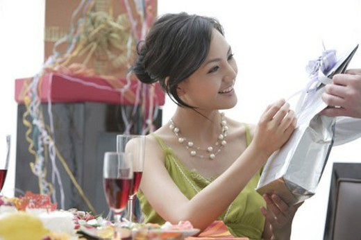 Young woman opening gift : Stock Photo