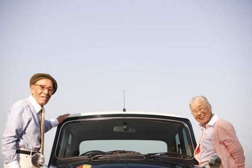 Stock Photo: 4029R-354469 Senior couple standing next to a car