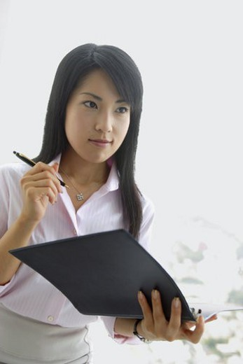 A woman holding a file stares at something : Stock Photo