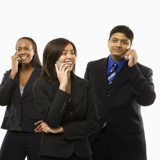 Stock Photo: 4029R-355206 Multi-ethnic businesswomen and businessman standing talking on cell phones.