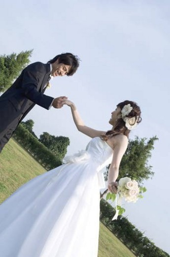 Stock Photo: 4029R-35540 Bride and groom holding hands outdoors
