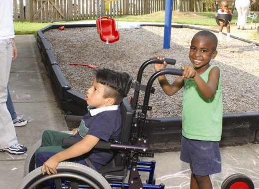 Stock Photo: 4029R-355661 Two adorable little boys playing on the playground.  The child without a disability is giving his friend who uses a wheelchair some assistance to get from one place to another.