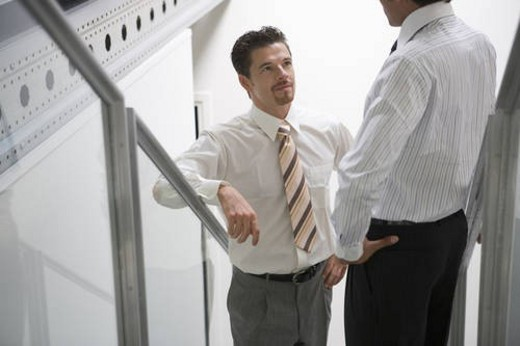 Two men talking on stairs in office, front view, rear view : Stock Photo