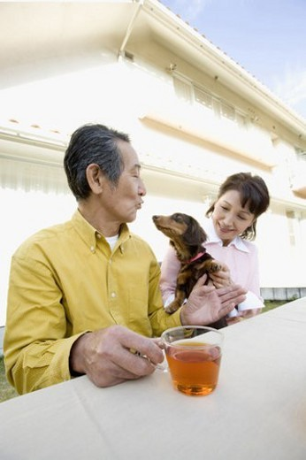 A Senior Adult Couple Having a Tea Break with a Dog in a Garden, Side View : Stock Photo