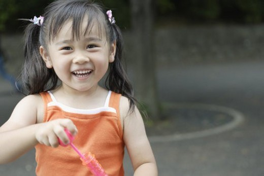 Stock Photo: 4029R-357363 Smiling girl holding bubble gun