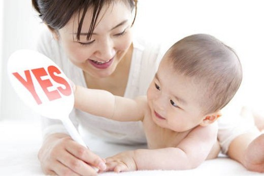 Mother and baby boy with sign reading  yes : Stock Photo