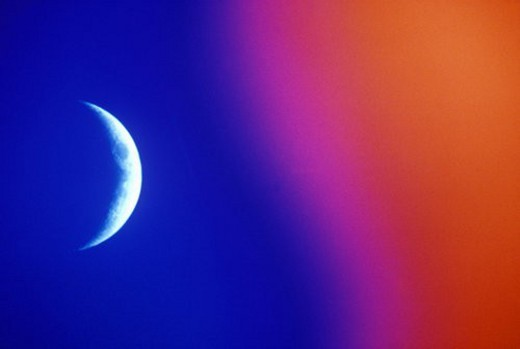 A crescent moon against a sky fading from blue to orange : Stock Photo