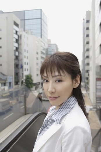 A woman looking at the camera as a commercial area is seen at the back : Stock Photo