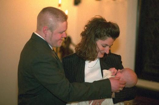 Uncle and aunt godparents holding newly baptized nephew : Stock Photo