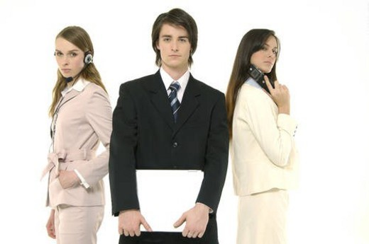 Stock Photo: 4029R-359158 Portrait of a businessman holding a laptop with two businesswomen standing behind him