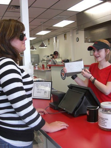 A woman, who is visually impaired, pays for her food after eating at her favorite restaurant. : Stock Photo