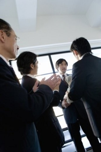 Image of Three Businessmen Congratulating to another Businessman with Applause, Low Angle View, Three Quarter Length : Stock Photo