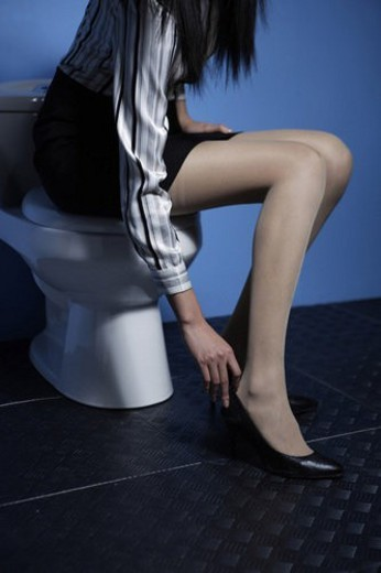 Business young woman sitting on a closestool, hands touching heels : Stock Photo