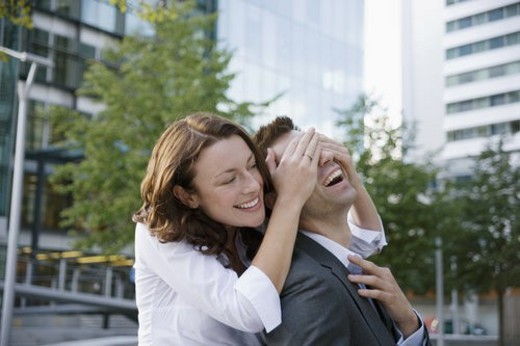Woman surprising man from behind : Stock Photo