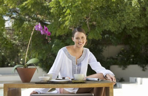A young woman sitting at a table : Stock Photo