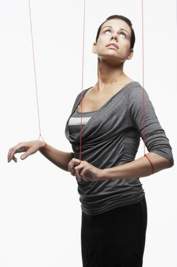 Mid adult woman as marionette looking up : Stock Photo