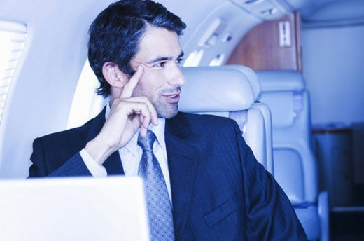 A businessman sitting on a plane : Stock Photo
