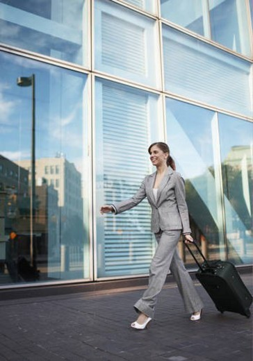 Mid-Adult Businesswoman Pulling Suitcase : Stock Photo