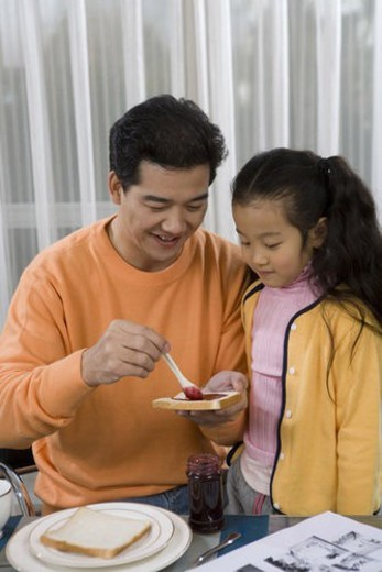 Father preparing bread to daughter : Stock Photo